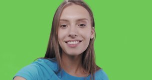 Young smiling woman in blue dress posing on green screen background. Girl taking selfie self portrait photo on smartphone. Chroma key. Female model showing positive face emotions. 4k raw video footage