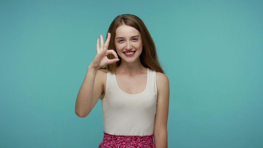 Okay, completely agree! Cheerful friendly girl showing ok gesture and smiling, laughing carefree at camera, satisfied with suggestion, success or winning concept. studio shot isolated, blue background