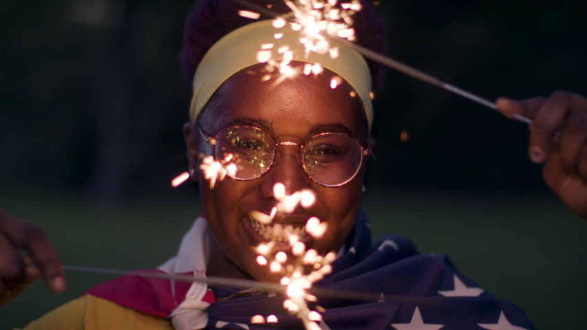 African American woman smiles draped in the flag-waving sparklers. Shot in slow-motion and in 4k.