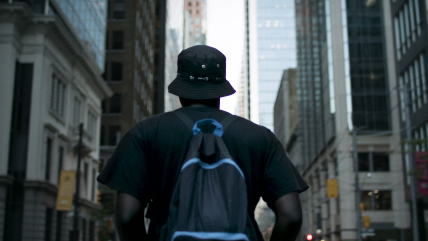 Fashionable African American man walks through the empty streets of a major downtown financial district. Shot in 4k Royalty-Free Stock Footage #1055128775