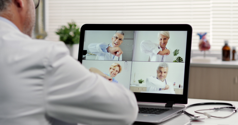 social distancing doctor makes a video call conference with his workteam online,group of doctors talking on livestream chat app greeting with an elbow bump Royalty-Free Stock Footage #1055129807