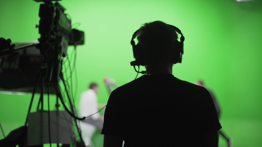 Film crew in green studio shooting video. Chroma - technology of combining two or more images or frames in single composition. Cameraman,director,crew. Filmmaking industry. | Shutterstock HD Video #1055129981