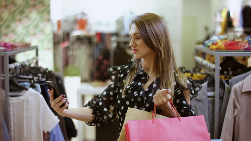 Young attractive woman is taking a selfie on smartphone camera with shopping bags at clothing store at mall