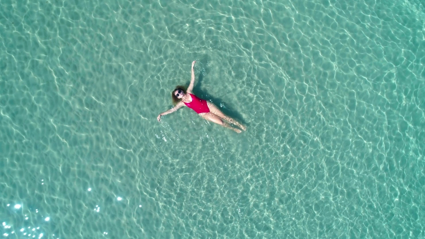 Top view of young pretty sexy girl in red swimsuit floating on water surface in crystal clear turquoise ocean. Happy island lifestyle. Vacation at Paradise. Ocean relax, travel to Philippines | Shutterstock HD Video #1055139095