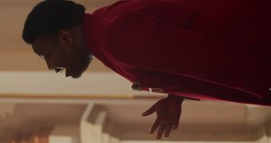 Side view of talanted african american gospel musician in red suit singing. Young man emotionally performing worship music and moving body in rhytm .Vertical video.