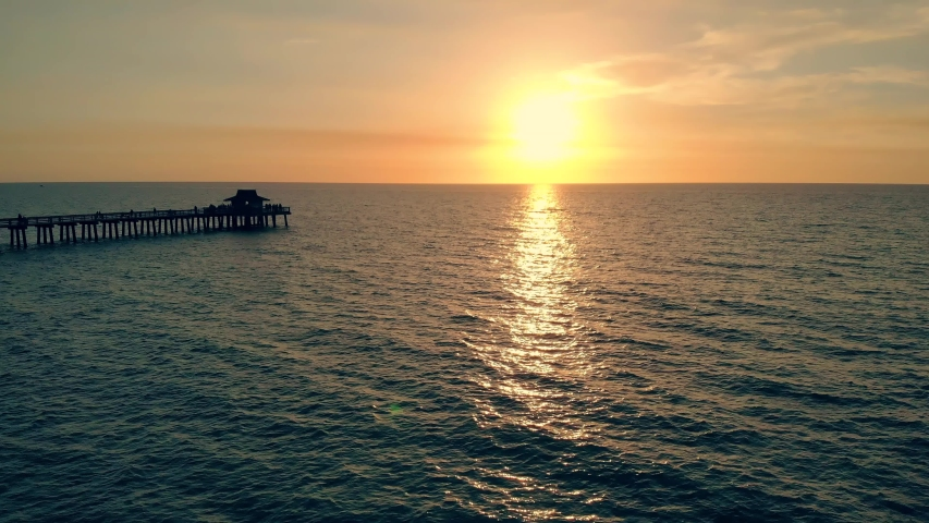 Fly back aerial shot of the silhouette of a fishing pier on the ocean with a colorful and golden sunset. Naples Beach and Fishing Pier at Sunset, Florida. Drone flies back, flying away from the pier. | Shutterstock HD Video #1055139857