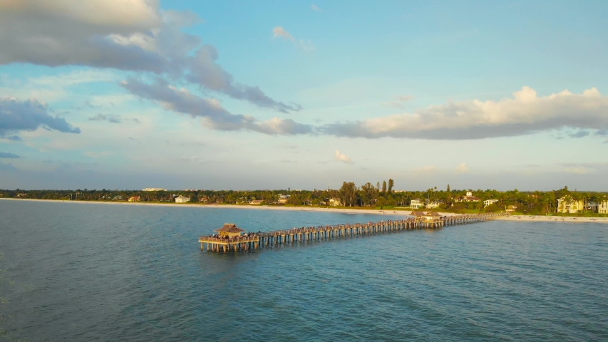 Pier in Naples by Aerial Drone. Drone flies around a fishing pier in Naples, Florida USA. Sunset over horizon and wooden pier of caribbean beach of Naples in Florida. Golden sunset with fishing pier. | Shutterstock HD Video #1055139860