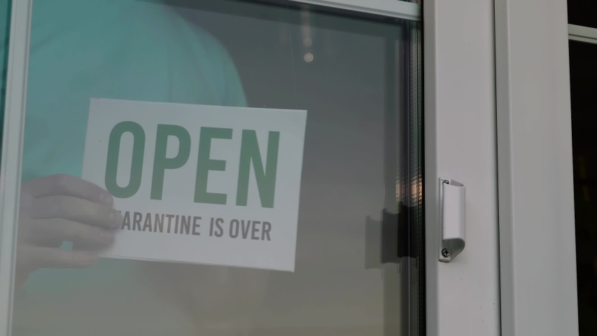 Close up of the male Caucasian hands turning a signboard on the glass door of the shop from CLOSED to OPEN. Reopening of a small business activity after quarantine covid-19 emergency. | Shutterstock HD Video #1055139875