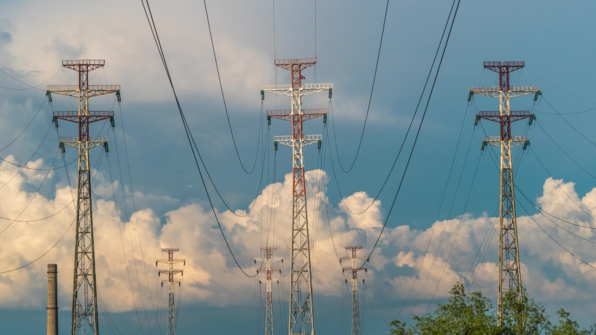 Electricity pylons cloud timelapse nature energy station electric poles the background of beautiful cloudy sky. Electricity station electric power plants and time lapse of high-voltage power lines.