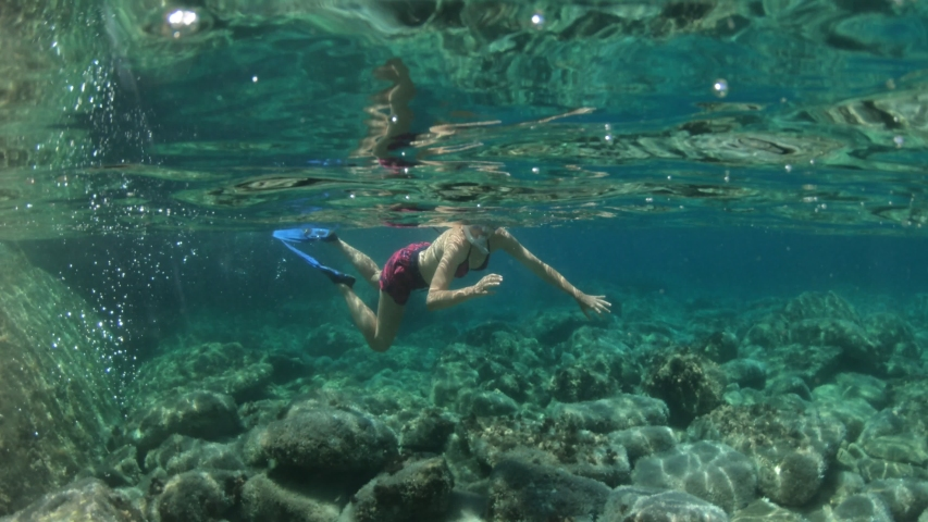 Woman snorkeler in Saint Andrew beach with reef and fishes of Elba island. Woman underwater snorkeling in Tyrrhenian sea on holiday travel, Italy. Saint andrew is Tuscan archipelago NP marine reserve.