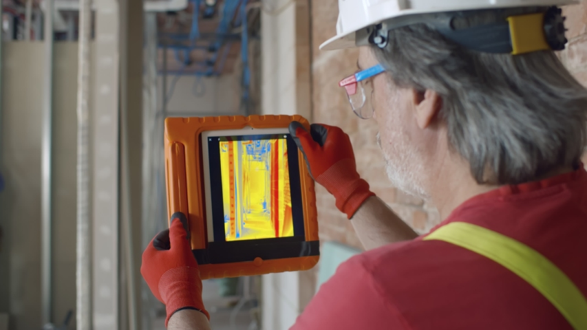 Close up back view of mature foreman in protective hardhat using thermal camera on digital tablet checking thermal insulation strength on construction site Royalty-Free Stock Footage #1055142575