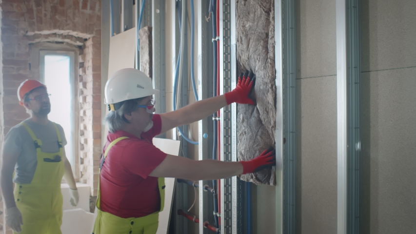 Construction workers in hardhats and gloves installing mineral wool in metal frames on wall during renovation works. Builders insulate walls indoors with fiber material Royalty-Free Stock Footage #1055142620
