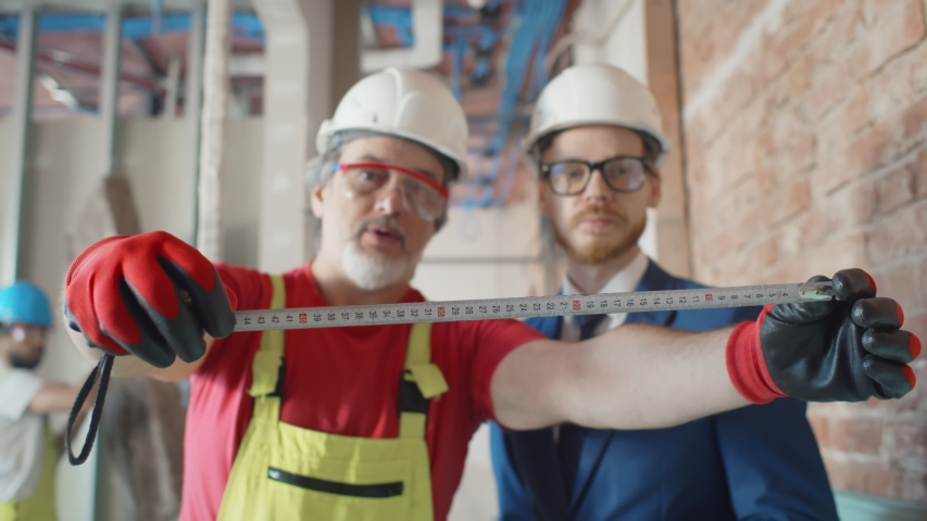 Close up portrait of mature foreman and young entrepreneur using measuring tape on construction site. Builder demonstrating contractor measurement with ruler | Shutterstock HD Video #1055142650