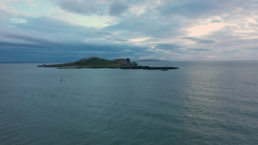 Aerial view of Ireland's Eye island viewed from the Howth harbor at sunrise on a cloudy day.Small uninhabited island off the coast of County Dublin | Shutterstock HD Video #1055142863