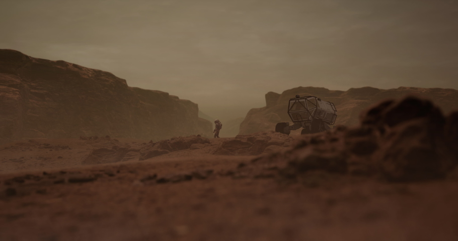 Astronaut walking near planet rover vehicle on a surface of a red rocky planet. Mars colonization concept. Dust effect added