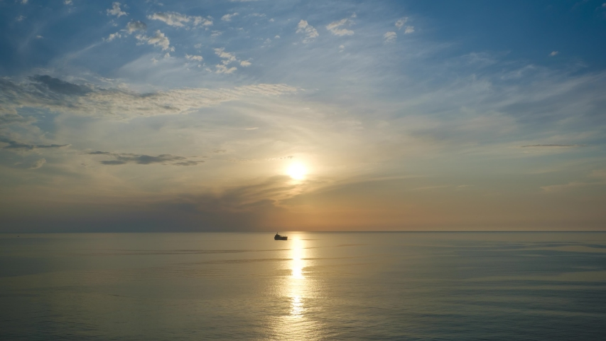 Romantic colorful sunset at the sea. Against the background of the sea, the sun goes down, blue and orange clouds flow in sky. Majestic summer landscape. landscape time lapse of sunset