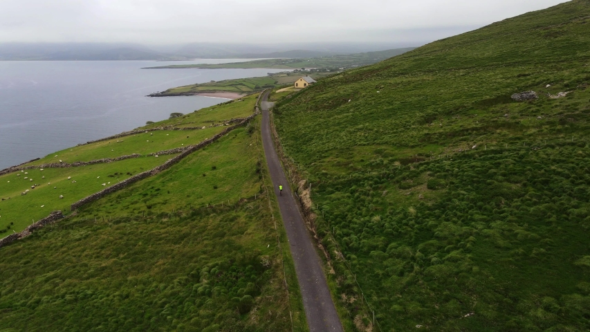 Ariel view of the Brandon Point, Co. Kerry. Ireland. Drones  following a cyclist on the narrow road on the Wild Atlantic Way.   Shutterstock HD Video #1055148083