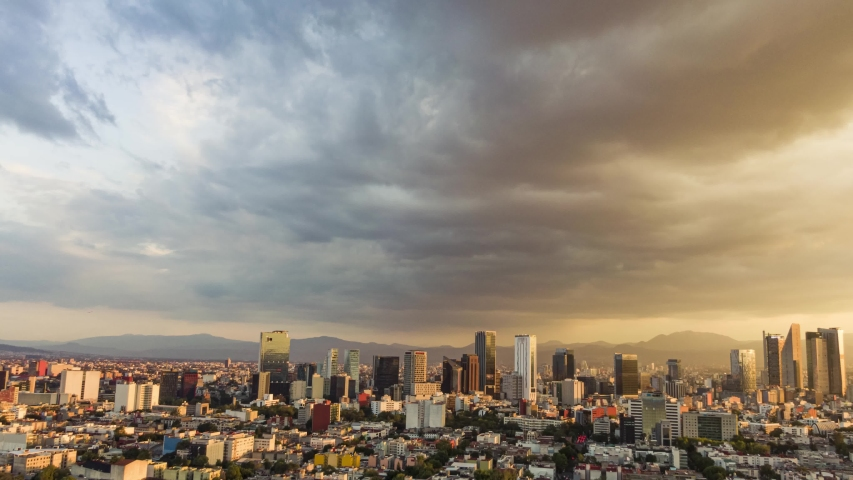 Hyperlapse top view flies over business, industrial and financial district of Mexico City, with skyscrapers of Paseo de la Reforma, on a dramatic cloudy day during the golden hour before sunset