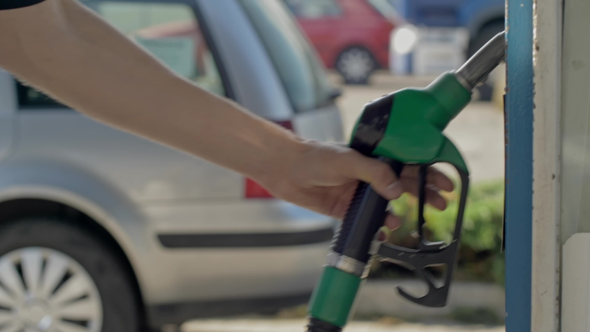 Close up of hand and fuel nozzle. Fuel nozzle getting put into its place.   Fuel, gas station, petrol prices concept. Gasoline, gas, fuel, petroleum concept.