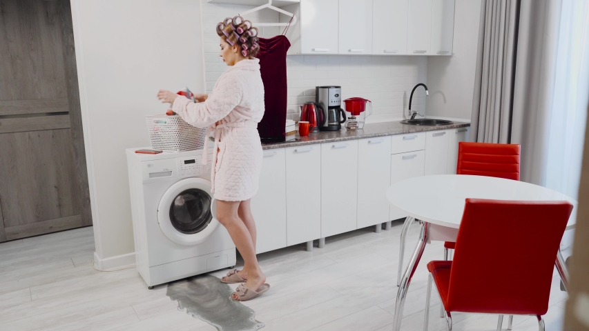 An agitated woman in a panic grabs the dress and wipes the water while the water flows from under the washing machine in the kitchen. A housewife who has a leak in the kitchen. Woman having washer Royalty-Free Stock Footage #1055149772