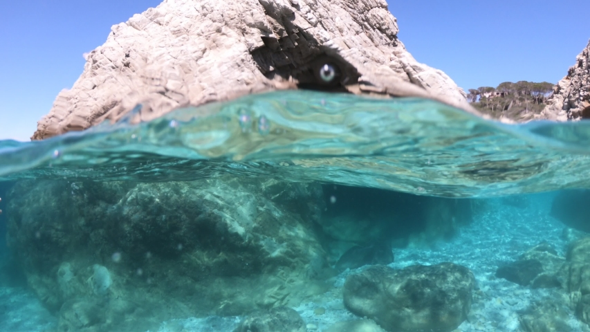 Split view underwater: woman snorkeler in Sansone beach on reef with tunnel of Elba island. Woman in waters of Tyrrhenian sea on holiday travel, Italy. Sansone is a Tuscan National Park marine reserve