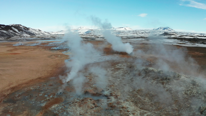 Namafjall Hverir geothermal area in Iceland. Stunning landscape of sulfur valley with smoking fumaroles and blue cloudy sky. Aerial view Royalty-Free Stock Footage #1055155076