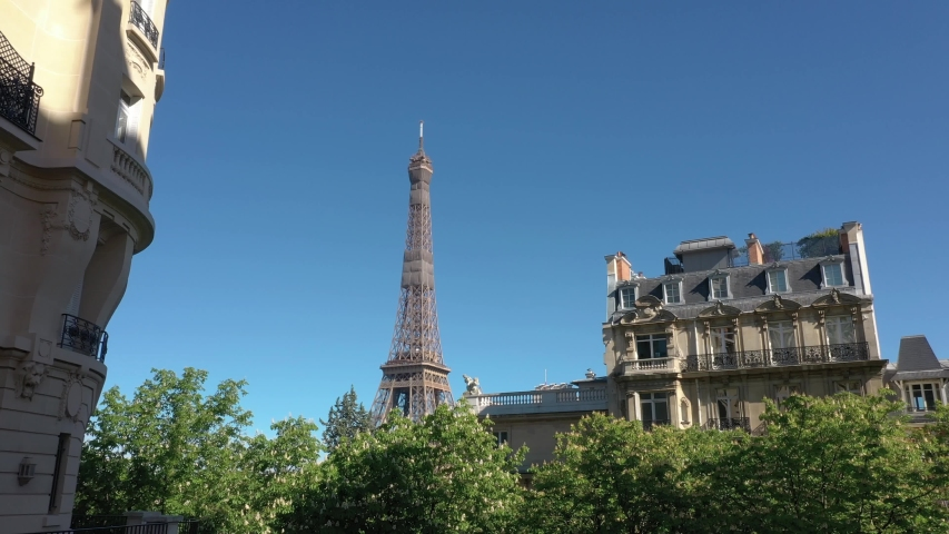 France, Paris, Tour Eiffel (Eiffel tower) with blue sky, green trees and haussmannien buildings in the foreground. 4k quality shot, aerial view from bottom to top (looks like crane or drone shot)   Shutterstock HD Video #1055158151