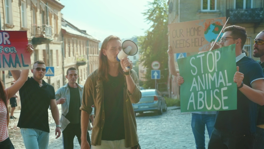 Inspiring man leader agitating crowd with loudspeaker outdoors. Multi-ethnic active urban youth protesting for animal rights and safe ecology in public demonstration. | Shutterstock HD Video #1055158220