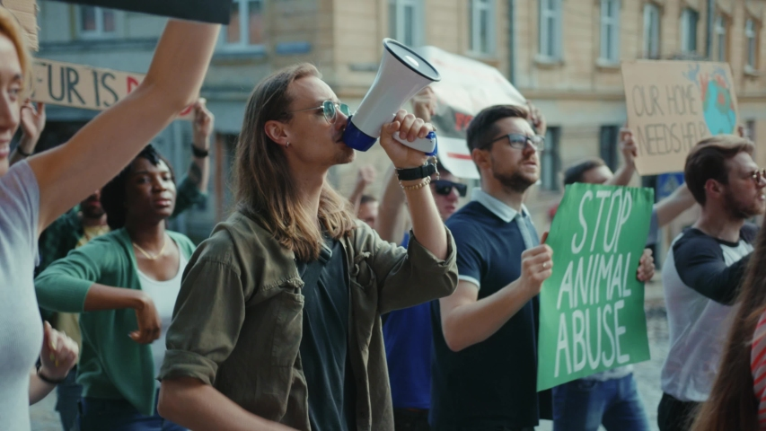 Inspiring man leader agitating crowd with loudspeaker outdoors. Multi-ethnic active urban youth protesting for animal rights and safe ecology in public demonstration. | Shutterstock HD Video #1055158226