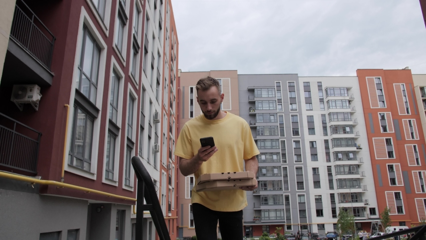 Courier in a yellow T-shirt delivers pizza online pizza delivery deliveryman calls the customer on the background of colored houses | Shutterstock HD Video #1055160029