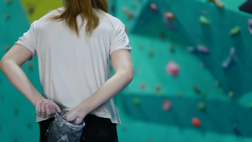 Fitness, extreme sport, bouldering, people concept - Caucasian female bouldering at an indoor climbing centre. Enthusiastic climber practicing rock climbing at an indoor climbing gym. 4K UHD | Shutterstock HD Video #1055161157