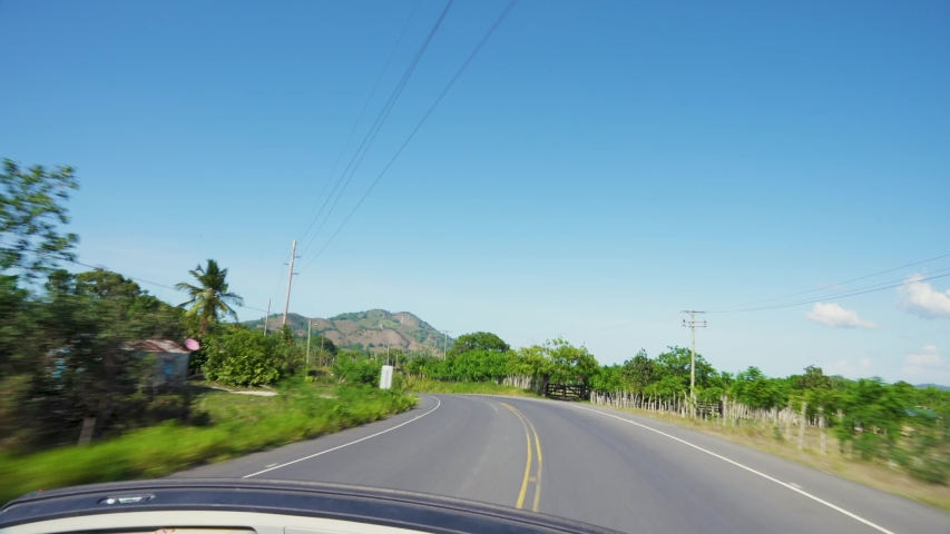 Summer travel concept. Dominican Republic convertible trip towards Mount Redonda. The car rides on the road among the mountains. Summer vacation on the island. | Shutterstock HD Video #1055162207