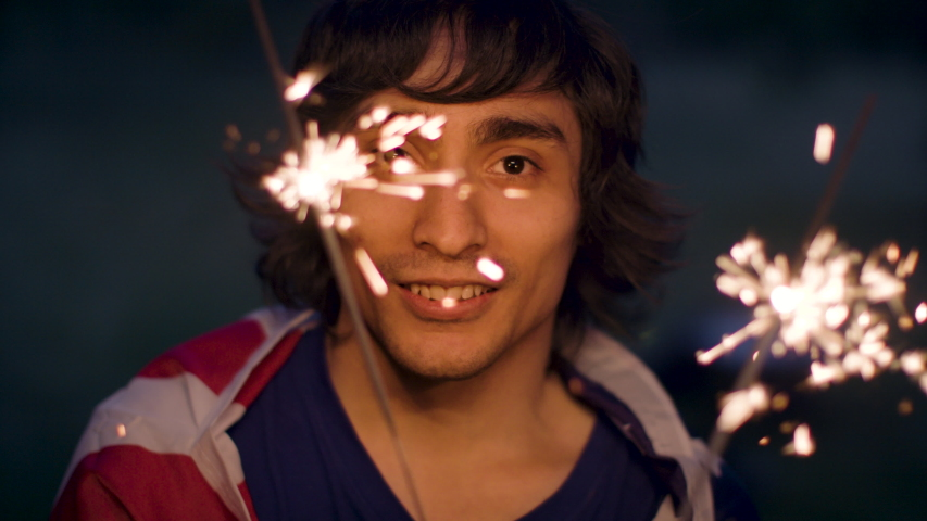 Celebrating Independence Day with sparklers. Man of Latin American descent enjoys 4th of July. Shot in slow-motion in 4k.