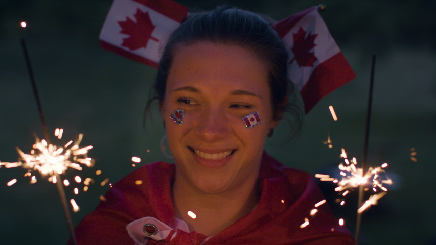 A caucasian woman celebrates Canada day with sparklers and miniature flags in her hair. Slow-motion and shot in 4k.