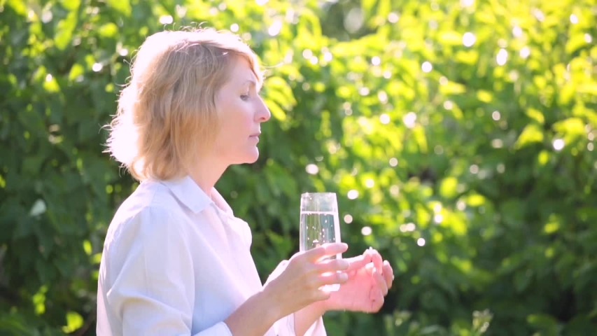A woman takes a pill against a background of greenery | Shutterstock HD Video #1055166206