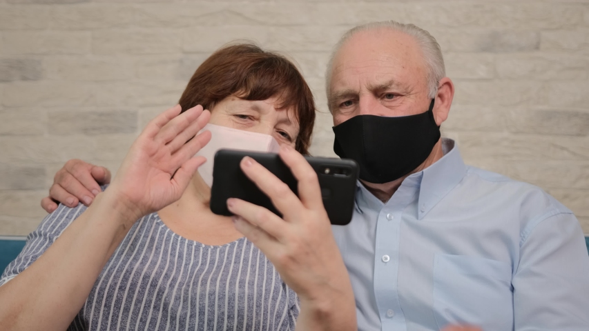 Senior couple talking on video chat with their children, sitting on sofa and wearing a medicinal mask to prevent virus spread Royalty-Free Stock Footage #1055166281