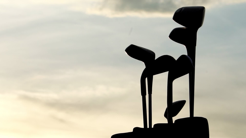 Footage Slow Motion: Golfer holding Golf clubs in golf clubs bag with sunset