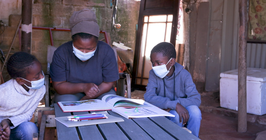 Black African woman home schooling her two young children at their dilapidated home during lockdown for Covid-19 Coronavirus pandemic, South Africa | Shutterstock HD Video #1055167967