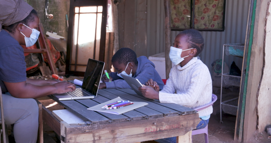 Poverty.Inequality.Black African woman using a laptop and digital tablet to home school her two young children at their dilapidated home during lockdown for Covid-19 Coronavirus pandemic, South Africa Royalty-Free Stock Footage #1055167979