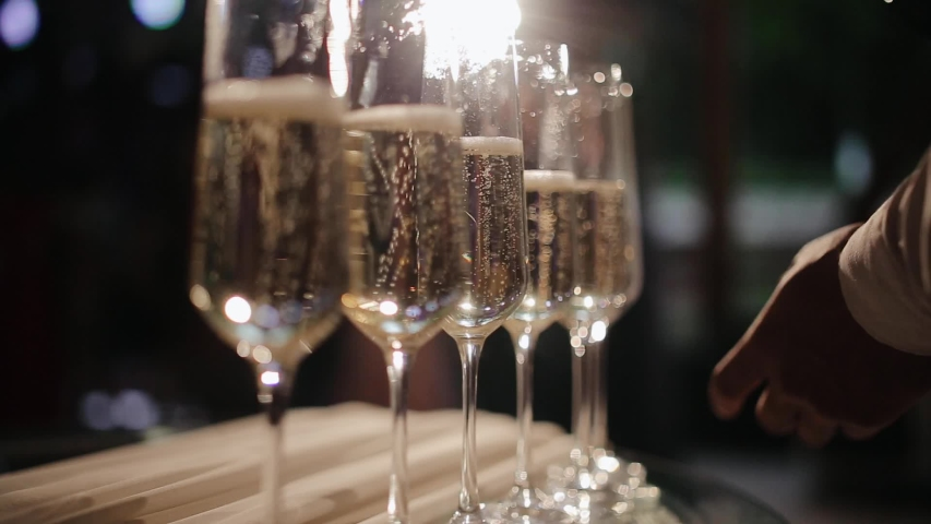 Waiter is pouring champagne. Pour the champagne into a glass. Bartender pouring champagne into glass, close-up. Champagne pouring in glass.