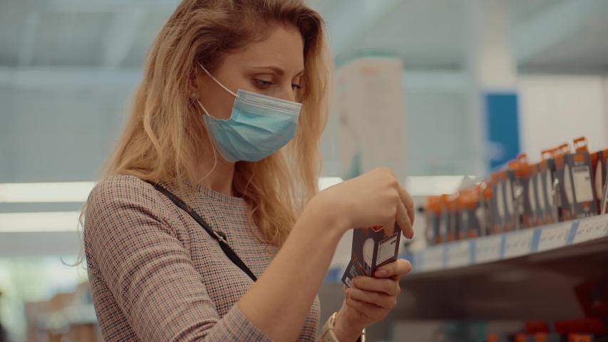 Girl In Face Mask Shopping In Market On Covid19 Coronavirus Pandemic Quarantine Lockdown.Woman Shopper Choosing Product In Hypermarket Store.Buyer In Face Mask In Supermarket Lockdown Self Distance. Royalty-Free Stock Footage #1055174207