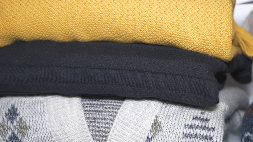 A close up panning view of folded stacks of men's jumpers. | Shutterstock HD Video #1055174813