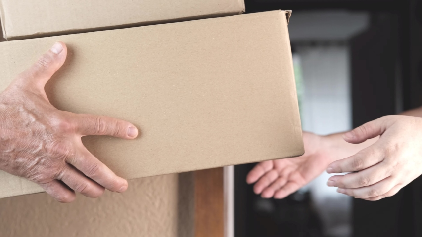 Uniform worker brought a parcel to the address and gives it to customers, delivery of ordered goods, online shopping concept | Shutterstock HD Video #1055176205
