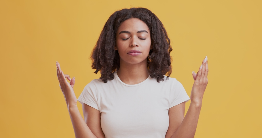 Harmony and peace concept. African american woman meditating with closed eyes and holding fingers in mudra gesture, orange studio background | Shutterstock HD Video #1055176730