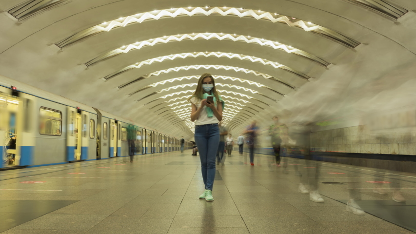 Woman Wearing Mask Standing Still in Underground Metro Station and Using Smartphone during Coronavirus Covid-19 Pandemic. Crowd of People and Passing Trains. Time Lapse Royalty-Free Stock Footage #1055177369