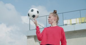Teenager girl football soccer player practicing tricks, kicks and moves with ball on rooftop empty parking garage. Urban city lifestyle outdoors concepte. 4K UHD slow motion RAW graded footage