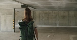 Teenager girl football soccer player walking inside empty covered parking garage. Skater holding skateboard. Back view. Urban city lifestyle outdoors concepte. 4K UHD slow motion RAW graded footage