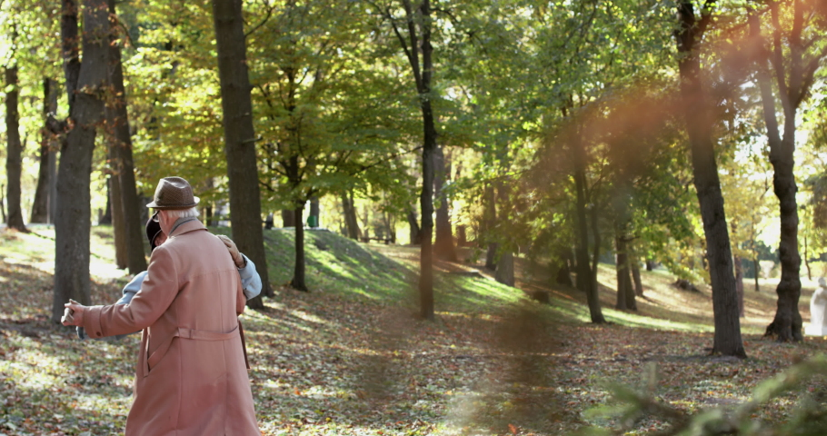 Elderly married couple in love dressed in coats and hats dancing elegant slow dance and having fun, they smiling in autumn park. Slowly in 4K