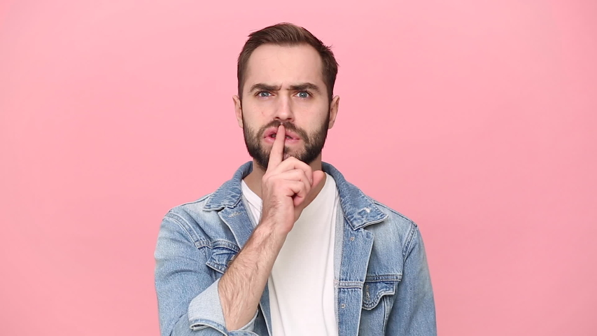 Strict young guy 20s years old in denim jacket white t-shirt isolated on pastel pink background studio. People lifestyle concept. Looking camera saying hush be quiet with finger on lips shhh gesture   Shutterstock HD Video #1055184218
