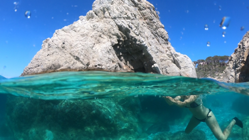 Split view underwater: woman snorkeler in Sansone beach on reef with tunnel of Elba island. Woman in waters of Tyrrhenian sea on holiday travel, Italy. Sansone is Tuscan archipelago NP. marine reserve